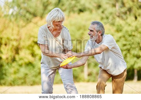 Active senior citizens playing with flying disk and having fun in the summer