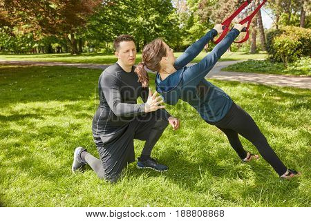 Woman makes sling training or suspension training at the park
