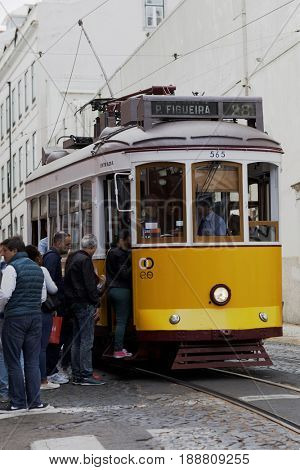 LISBON, PORTUGAL - MAY 9, 2017: People at the vintage tram near Saint Vincent church. First electric tramway in the city commenced operations in 1901, and now the system comprises five urban lines