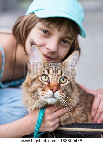 Happy little girl hugging lovely kitten. Cute ten year old child playing with her cat with leash - close up, focus on kitten. Outdoors portrait of beautiful kid with big fluffy Maine Coon kitty.