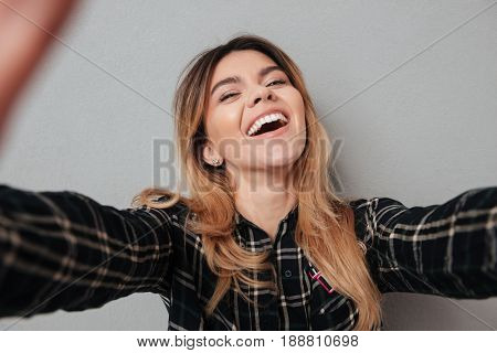 Happy lovely girl making selfie with mobile phone and laughing isolated over grey background