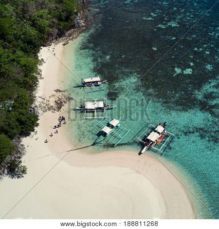 Aerial top view of tropical island beach with boats and people. Palawan May 2017