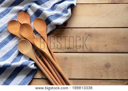 Wooden mixing spoons and dish towel on a wooden table top.