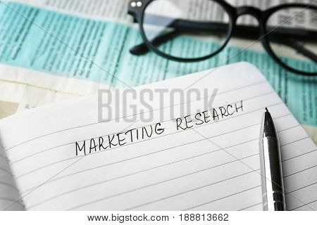 Open notebook with text MARKETING RESEARCH, closeup