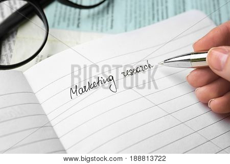 Woman writing text MARKETING RESEARCH in notebook