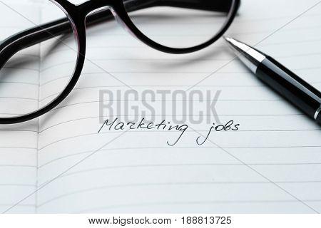 Open notebook with text MARKETING JOBS, closeup