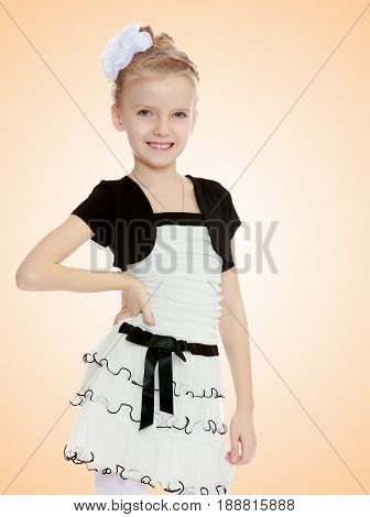 Beautiful little blonde girl dressed in a white short dress with black sleeves and a black belt.Closeup.