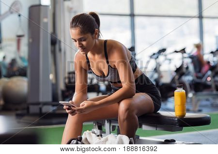 Young woman athlete using cell phone at gym. Latin woman in sportswear checking phone while resting after workout on bench. Beautiful fit girl messaging with smartphone at fitness centre.