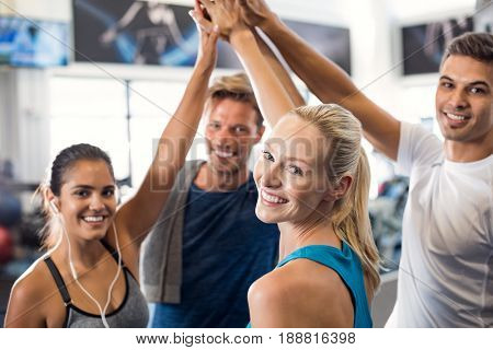 Happy fitness class giving high-five after completing exercise session. Group of sporty people giving high five and looking at camera. Smiling friends celebrate their success.