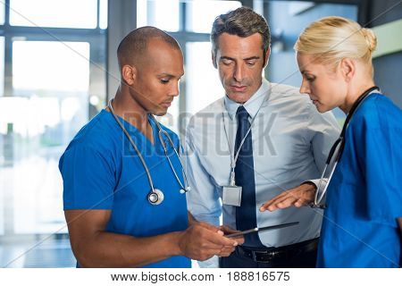Medical team interacting using digital tablet at modern hospital. Mature doctor and african surgeon working on digital tablet with nurse. Head physician working with his medical team at clinic.