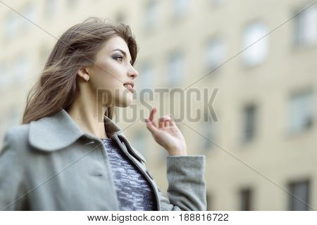 Young pretty girl, spring outdoor portrait. Beautiful woman against the backdrop of the urban landscape