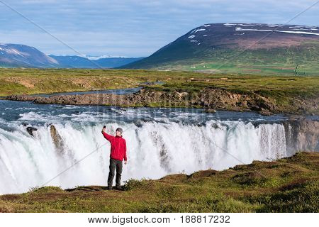 Godafoss waterfall. Beautiful landscape in Iceland. Guy in a red jacket makes a selfie near the river