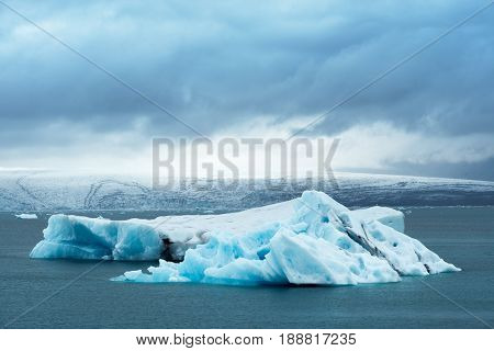 Landscape of Iceland, Europe. Iceberg in glacial lagoon, located in the southeastern part of the island, near the glacier Vatnajokull. Tourist attraction. Cloudy day in the middle of the month June
