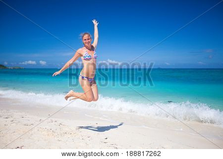 Happy girl in bikini jumping on beach