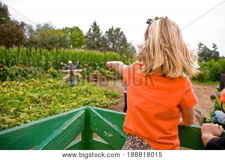 GRANITE BAY, CALIFORNIA, USA - October 18, 2009: Young blonde girl points at scarecrow while rinding in a green wooden wagon at a farm
