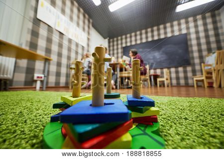 Children construction sets on floor covering in playroom of child club, shallow dof.