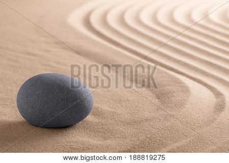 Zen meditation stone garden with rock on raked sand
