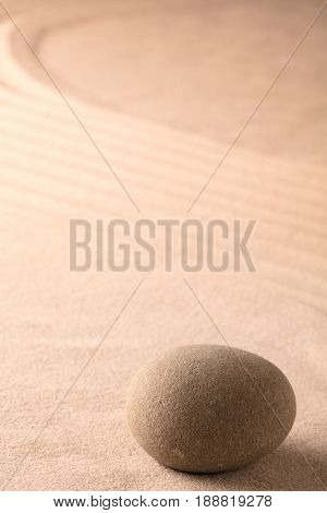 Zen meditation stone with raked lines in the sand. Yoga or spa wellness background with copy space.