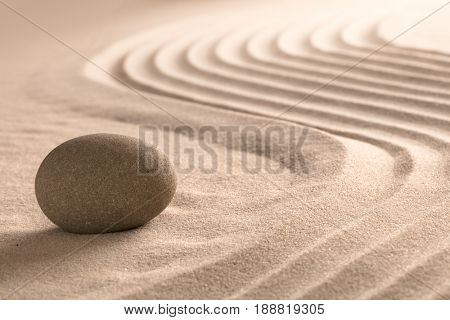 Yoga meditation zen background. Sand texture and round stone. Spa wellness theme.