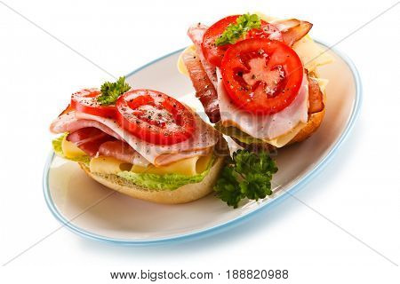 Sandwiches with meat, cheese and vegetables on white background