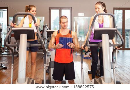 Women working out in a gym under the guide of a personal trainer