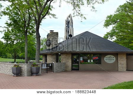 NAPERVILLE, ILLINOIS - MAY 26, 2017: Riverwalk Cafe. The restaurant on Napervilles Riverwalk with the Moser Tower and Millennium Carillon in the background.