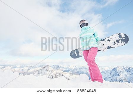 Female snowboarder wearing colorful helmet, blue jacket, grey gloves and pink pants standing standing with snowboard in her hands and preparing for ride - snowboarding concept, copy space