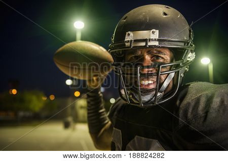 African American football player throwing the ball