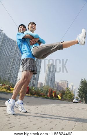 Chinese man lifting girlfriend in city