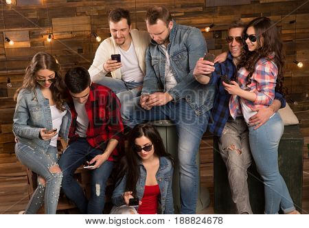 Group of  friends happy people, students with smartphones in their hands are watching social networks. Having fun on the Internet online. Positive girls and boys Friendship between men and women.