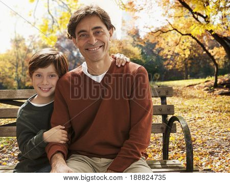 Caucasian father and son sitting on park bench
