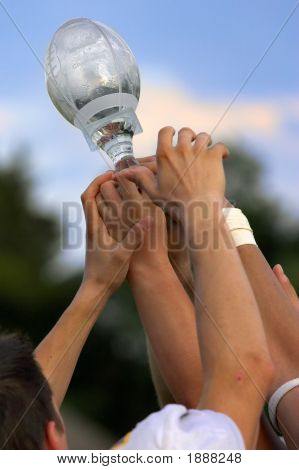 Hands reaching for a trophy after winning the championship game. poster