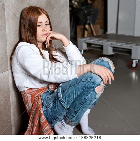 Bored young girl leaning against wall at home.