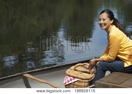Asian woman with picnic basket and canoe
