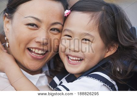Chinese mother hugging daughter in school uniform