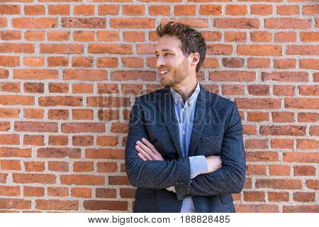 Confident business entrepreneur man young businessman looking to the side portrait against city office brick wall background. Smiling caucasian male professional in smart casual jacket.