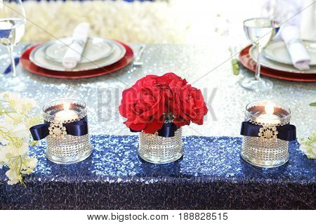 Flower arrangement with red roses and candles over sequence table