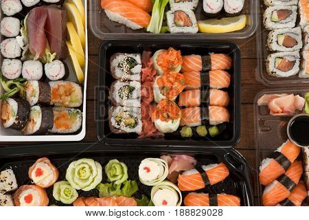 Assorted sushi set served in plastic boxes on wooden table