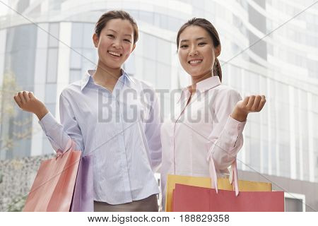 Smiling Chinese businesswomen carrying shopping bags