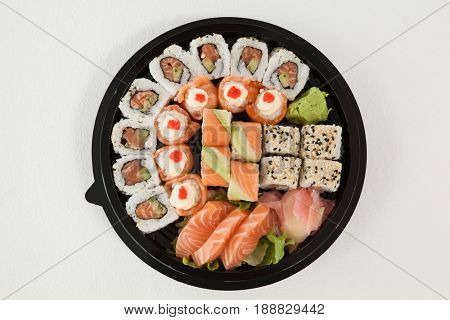 Set of assorted sushi kept in a round black box against white background