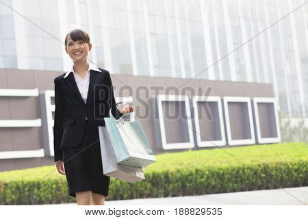 Smiling Chinese businesswoman carrying shopping bags