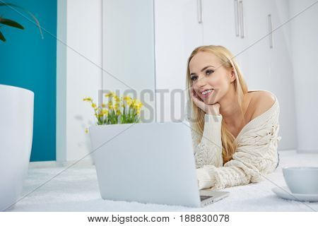 Beautiful woman working on laptop on white bedroom