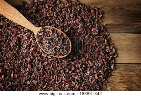 Heap of cocoa nibs and wooden spoon, closeup