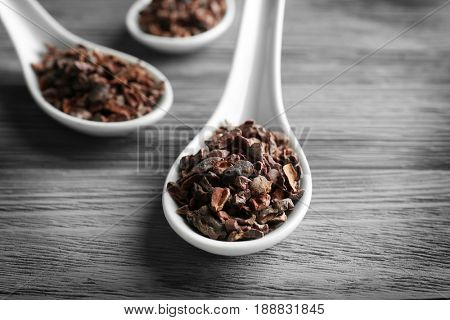 White spoons with cocoa nibs on wooden table