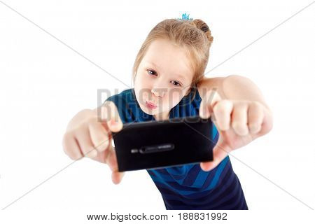 A little girl with a smartphone in her hands makes selfie
