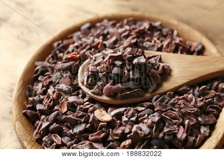Wooden bowl and spoon with cocoa nibs, closeup