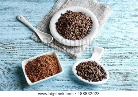 Composition with cocoa nibs and powder on wooden table