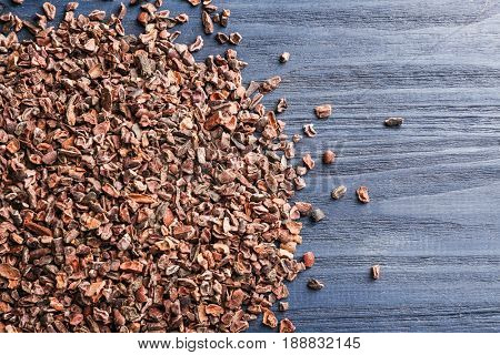 Heap of cocoa nibs on wooden background