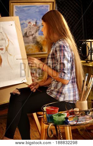 Artist painting on easel in studio. Girl paints portrait of woman with brush. Female draws self-portrait. Indoor home interior for handmade crafts. Female is carrying out order.