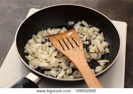 Frying pan with chopped onion, closeup